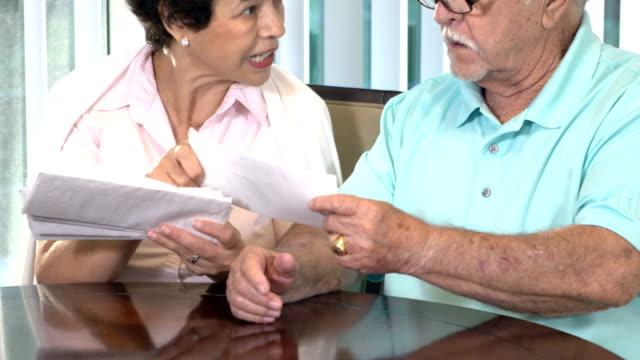 senior hispanic couple looking through bills - face to face stock videos & royalty-free footage