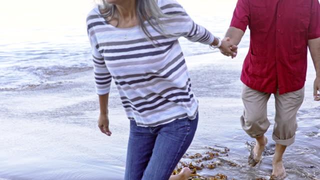 vídeos y material grabado en eventos de stock de pareja hispana senior caminando a lo largo de la playa - etnia