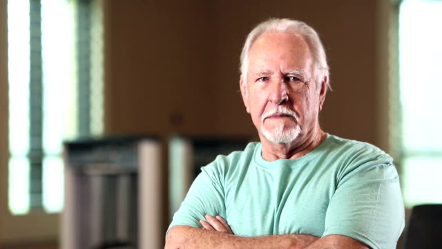 senior hispanic man looking at camera, serious to smile - t shirt stock videos and b-roll footage