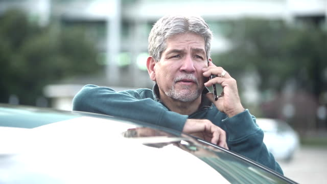 senior hispanic man on mobile phone in parking lot - leaning stock videos & royalty-free footage