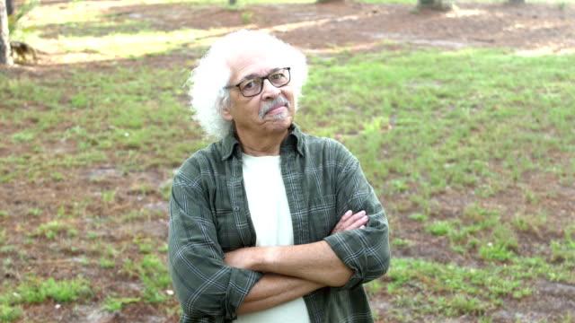 Senior Hispanic man standing in park