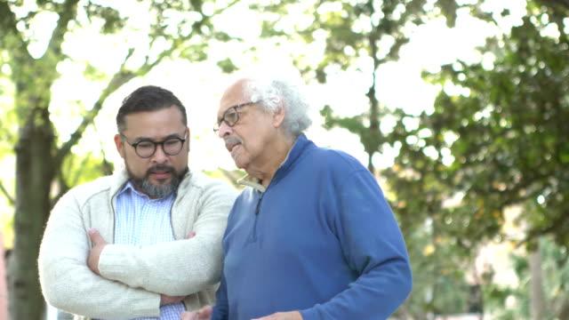 senior hispanic man walking, talking with adult son - adult offspring stock videos & royalty-free footage