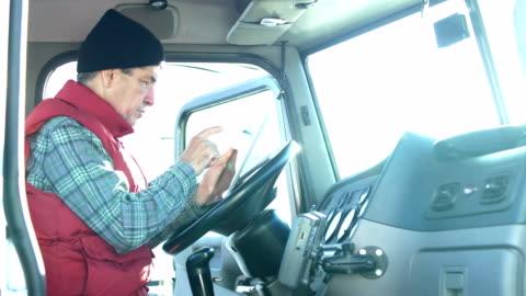 stockvideo's en b-roll-footage met hogere spaanse vrachtwagenchauffeur die digitale tablet gebruikt - commercieel landvoertuig
