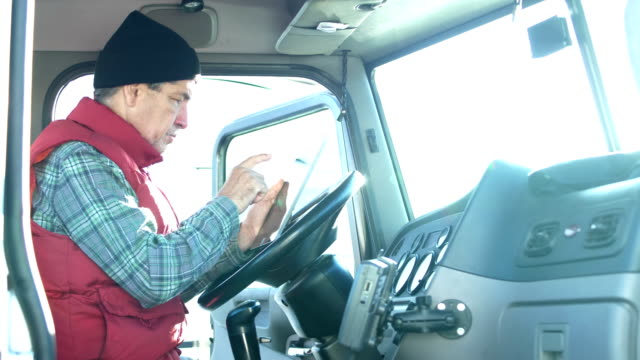 senior hispanic truck driver using digital tablet - commercial land vehicle stock videos & royalty-free footage