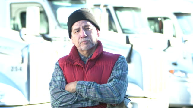 senior hispanic trucker standing by row of semi-trucks - 60 69 years stock videos & royalty-free footage