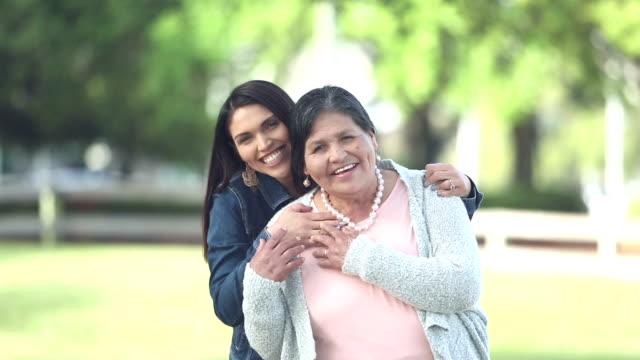 senior hispanic woman, adult daughter in park, hugging - simple living stock videos & royalty-free footage