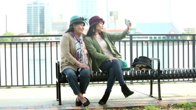 vidéos et rushes de femme hispanique aînée, fille, selfie dans des chapeaux élégants - chapeau