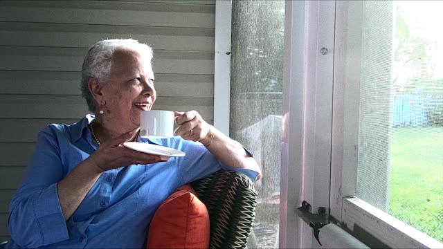 senior hispanic woman enjoying cup of tea or coffee - veranda stock videos & royalty-free footage