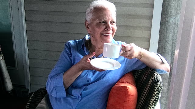 senior-hispanic frau tasse tee oder kaffee zu genießen - perlenohrringe stock-videos und b-roll-filmmaterial