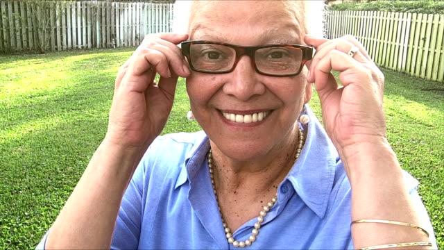 senior-hispanic frau im hinterhof, die brille aufsetzen - perlenohrringe stock-videos und b-roll-filmmaterial
