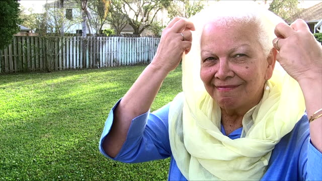 senior-hispanic frau im hinterhof kopftuch aufsetzen - perlenohrringe stock-videos und b-roll-filmmaterial