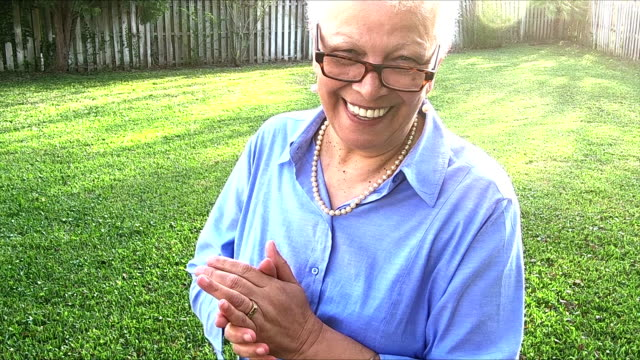 Senior Hispanic woman in back yard turns toward camera