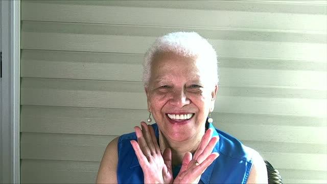 senior-hispanic frau entspannen auf der veranda, lachen - perlenohrringe stock-videos und b-roll-filmmaterial