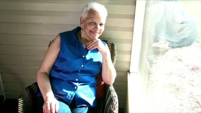 senior-hispanic frau entspannen auf der veranda - perlenohrringe stock-videos und b-roll-filmmaterial