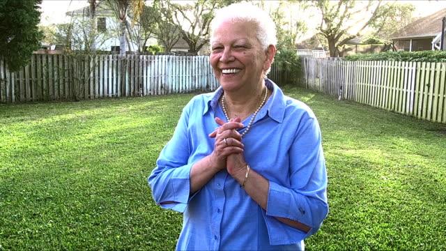 vidéos et rushes de femme senior hispanique, debout dans son yard arrière clôturé - clôture jardin