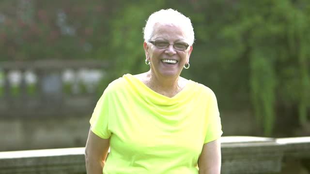 Senior Hispanic woman standing in park