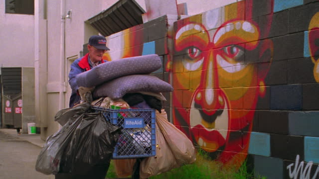 pan senior homeless man pushing shopping cart past wall with murals / los angeles - homelessness stock videos & royalty-free footage