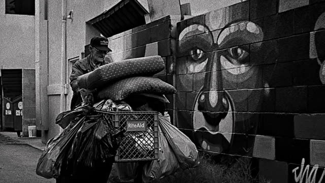 B/W PAN senior homeless man pushing shopping cart past wall with murals / Los Angeles