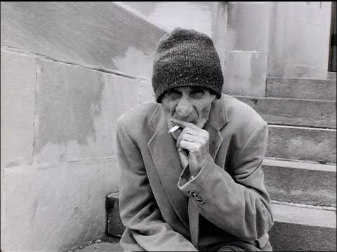 vidéos et rushes de b/w senior homeless man sitting on stairs + smoking / looks up towards camera - octogénaire et plus