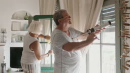 Senior Husband and Wife Cleaning and Caulking Home Windows