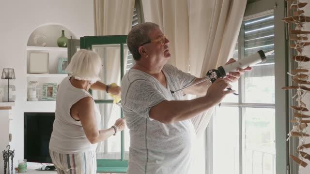 vídeos y material grabado en eventos de stock de senior husband and wife cleaning and caulking home windows - bricolaje