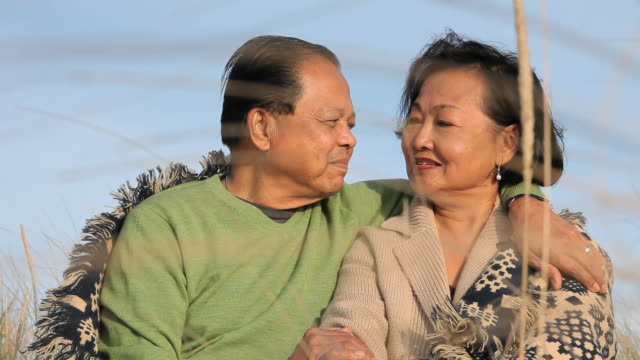 ms tu senior husband and wife sitting together under blanket on beach dunes / eastville, virginia, usa - eastville stock videos and b-roll footage