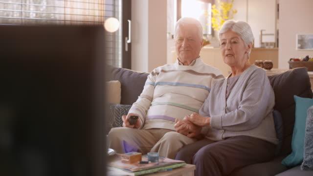 DS Senior man och hustru titta på TV och prata