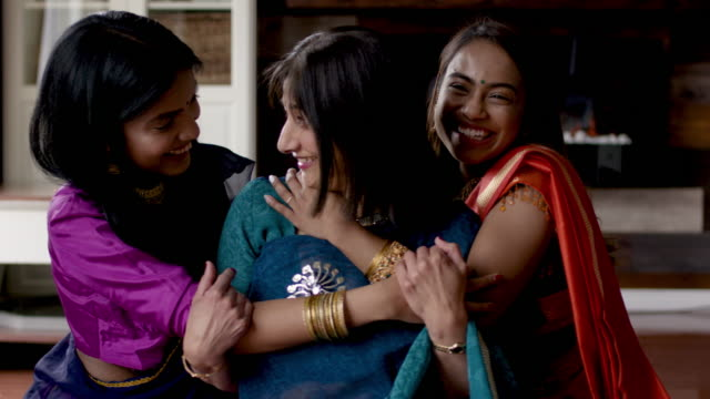 senior indian mother laughing together with adult daughters - maharashtra stock-videos und b-roll-filmmaterial