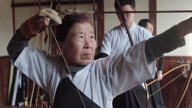 資深的日本弓箭手撫摸著她的箭, 開槍射擊 - 組織 個影片檔及 b 捲影像