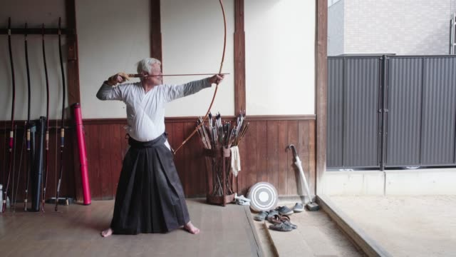 senior japanese archer taking aim and loosing his arrow - martial arts stock videos & royalty-free footage