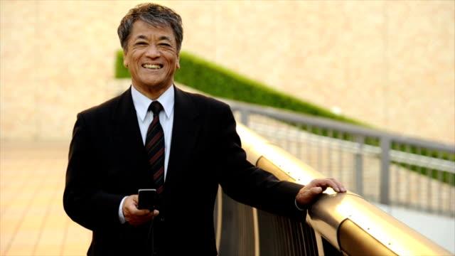 シニア日本の実業家のテキストメッセージ - senior men点の映像素材/bロール