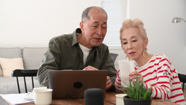 senior japanese couple doing home finances on laptop - silver surfer stock videos & royalty-free footage