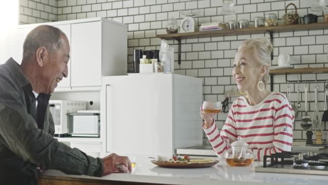 senior japanisches paar genießen eine nachmittags-tee-pause in der küche - älteres paar stock-videos und b-roll-filmmaterial
