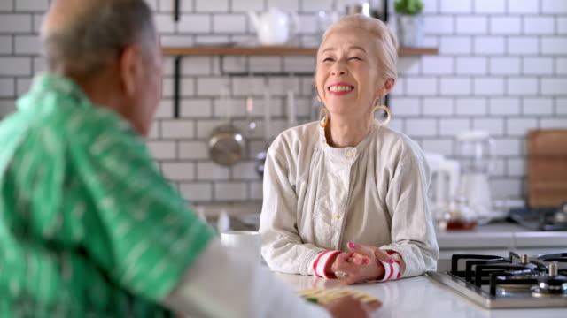 キッチンカウンターで朝食を楽しむシニア日本人カップル - 向かい合わせ点の映像素材/bロール