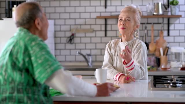 vidéos et rushes de couples japonais principaux appréciant le petit déjeuner au compteur de cuisine - jeune d'esprit