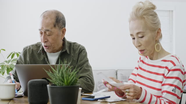senior japanese couple managing home finances at living room - saving up for a rainy day stock videos and b-roll footage