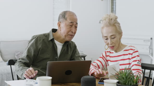 senior japanese couple managing home finances - saving up for a rainy day stock videos and b-roll footage