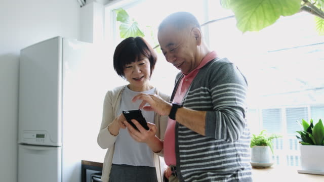 Senior Japanese Couple Playing With Smart Phone