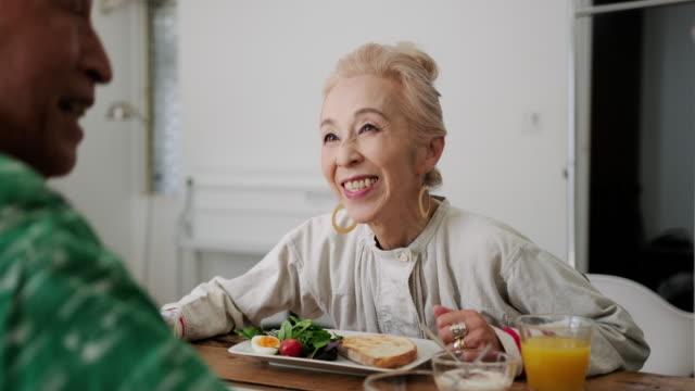朝食と良い会社を味わうシニア日本人カップル - 年配の女性点の映像素材/bロール