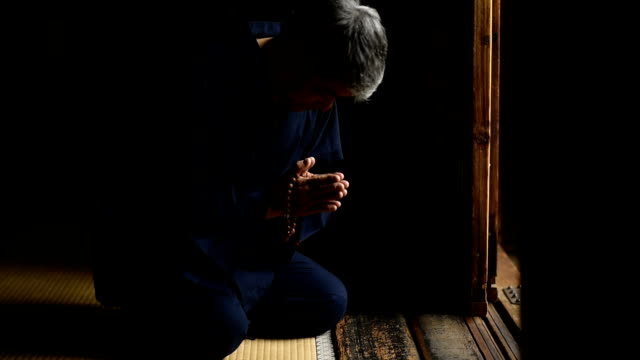 Senior Japanese man praying at a temple