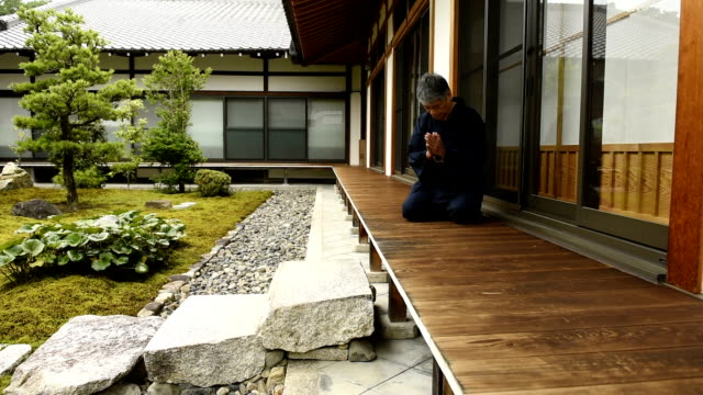 senior japanese man praying at a temple - oriental garden stock videos and b-roll footage