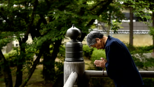 senior japanese man praying at a temple - shrine stock videos & royalty-free footage