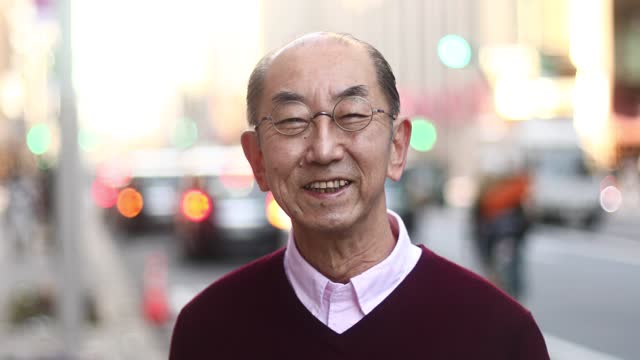 a senior japanese man smiles on the street in tokyo. - honesty stock videos & royalty-free footage