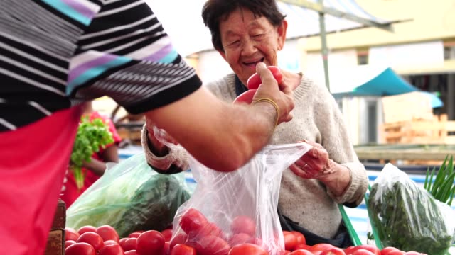 senior japanese woman customer and salesman at farmers market - agricultural fair stock videos & royalty-free footage