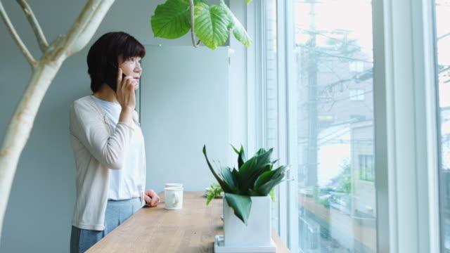 ウィンドウで電話で話している年配の日本女性