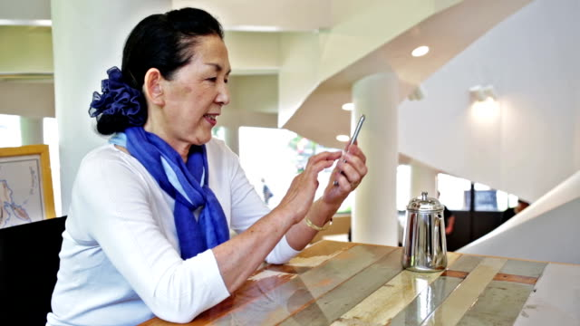 Senior Japanese Woman Using A Smart Phone