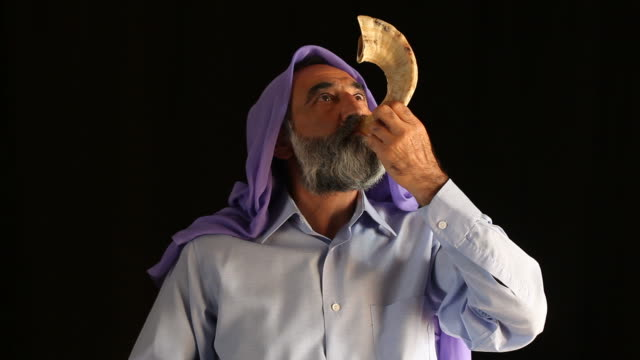 Senior jewish man playing shofar for religious holiday