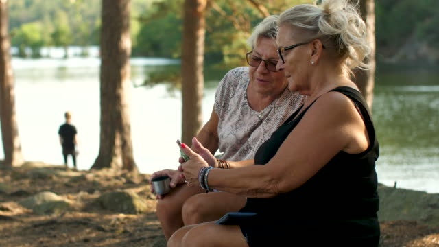 senior ladies using a smartphone in a forest - cozy stock videos & royalty-free footage