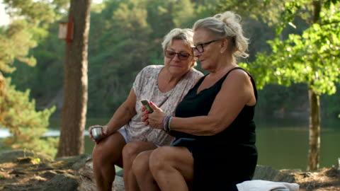 vídeos y material grabado en eventos de stock de señoras mayores usando un teléfono inteligente en un bosque - mature women