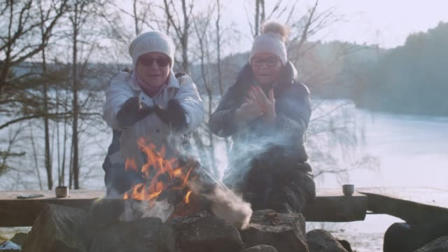 Senior ladies warm themselves by a fire